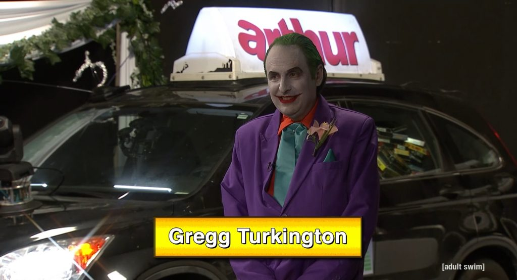 Gregg Turkington in a purple outfit, white facepaint, and green hair as the Joker