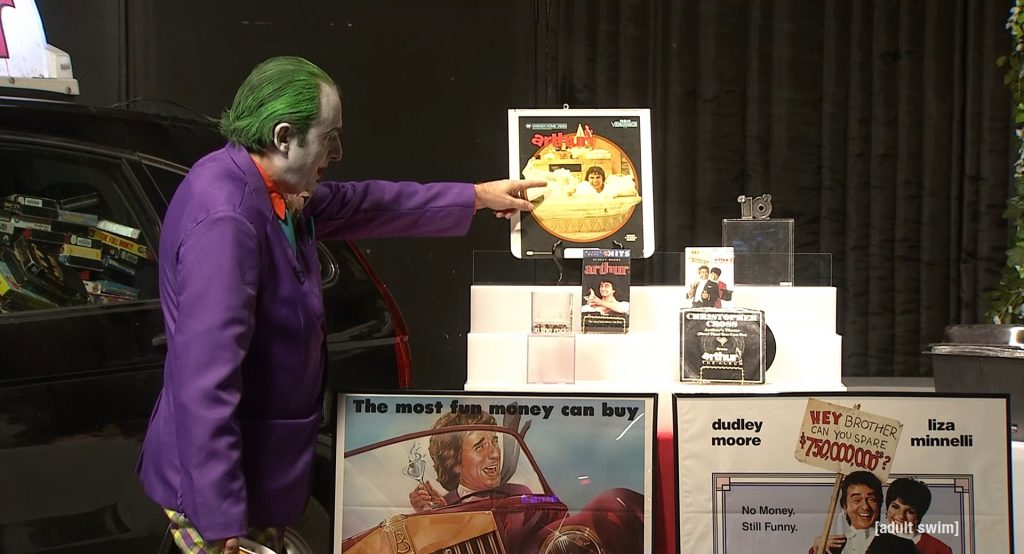 Gregg dressed as the Joker pointing out his Arthur memorabilia